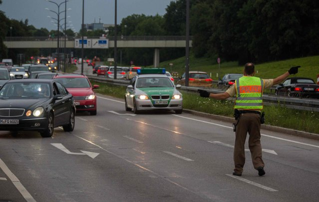 A policeman blocks the traffic at the exit near a shopping mall (the Olympia Einkaufzentrum (OEZ) ) in Munich on July 22, 2016 following shootings. German police were hunting for three gunmen who went on a shooting rampage in a Munich mall on Friday, killing eight people in what was described as a suspected terror attack. (Photo by AFP Photo/Stringer)