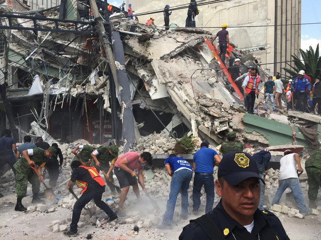 People search for survivors in a collapsed building in the Roma neighborhood of Mexico City, Tuesday, September 19, 2017. A powerful earthquake has jolted Mexico, causing buildings to sway sickeningly in the capital on the anniversary of a 1985 quake that did major damage. (Photo by Enric Marti/AP Photo)