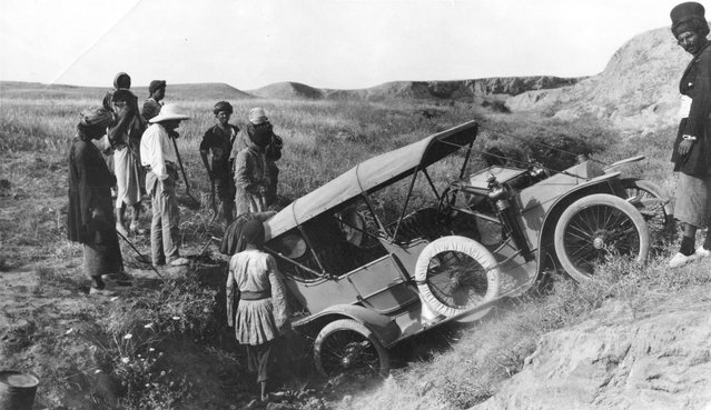 A car ends up in a ditch after being driven off the road, somewhere in Persia, circa 1925.