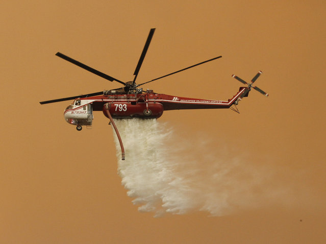A helicopter drops water on the Sand Fire near Wildlife Waystation on Little Tujunga Canyon Road, Calif., on Saturday, July 23, 2016. (Photo by Katharine Lotze/The Santa Clarita Valley Signal via AP Photo)