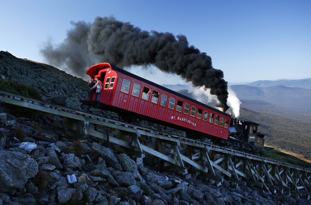 A vintage coal-fired steam engine pushes a passenger car up the Cog Railway on a 3.8-mile journey to the summit of 6,288-foot Mount Washington in New Hampshire, Sunday, September 24, 2017. Tourists visiting the northeast's highest peak were rewarded with summer-like weather on the first weekend of autumn. (Photo by Robert F. Bukaty/AP Photo)
