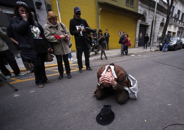 A fan reacts outside the clinic where Argentine musician Gustavo Cerati died today at the age of 55 in Buenos Aires September 4, 2014. Cerati was a flamboyant showman who brought stadium rock to Latin America with his band Soda Stereo. Grammy-winning Cerati had been in a coma since suffering a stroke in May 2010, after a show in Venezuela. (Photo by Marcos Brindicci/Reuters)