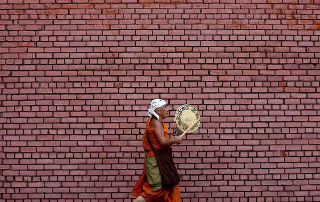 A monk plays a traditional musical instrument as he walks along a street in the early morning in Colombo, Sri Lanka May 16, 2017. (Photo by Dinuka Liyanawatte/Reuters)