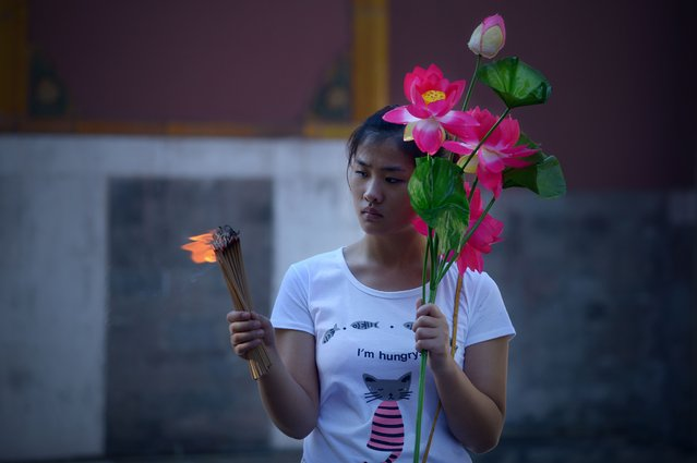 A woman holds a bunch of burning incense sticks and artificial flower during the Mid-Autumn festival at Lama Temple in Beijing on September 8, 2014.  As a tranditonal custom, thousands of Chinese people head to temples to offer prayers during the festival in Beijing. (Photo by Wang Zhao/AFP Photo)