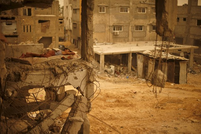 A Palestinian boy sleeps on a mattress inside the remains of his family's house, which witnesses said was destroyed by Israeli shelling during a 50-day war in 2014 summer, during a sandstorm in Gaza September 8, 2015. (Photo by Suhaib Salem/Reuters)