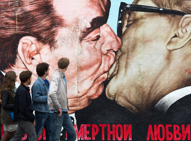 """Visitors walk in front of a painting dated 1990 and showing the Socialist fratenal kiss between former GDR leader Erich Honecker and former Soviet Union leader Leonid Brehnev titled """"My God, Help Me To Survive This Deadly Love"""" at the so-called Eastside Gallery, a part of the former Berlin Wall that once devided the city of Berlin, in Berlin, September 13, 2014. (Photo by Bernd Von Jutrczenka/EPA)"""