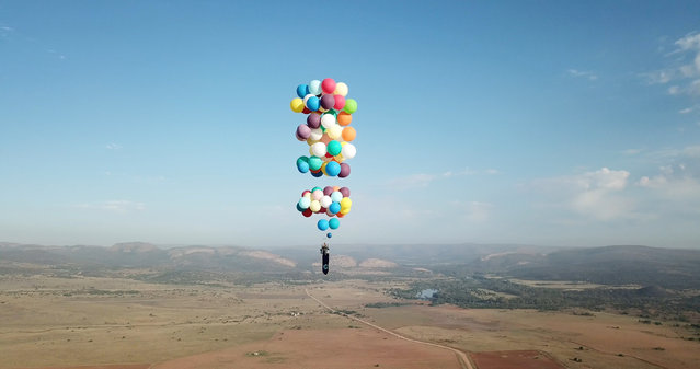 Tom Morgan, from Bristol-based company The Adventurists, flies in a chair with large party balloons tied to it near Johannesburg, South Africa, October 20, 2017. (Photo by Reuters/The Adventurists and Richard Brandon Cox)