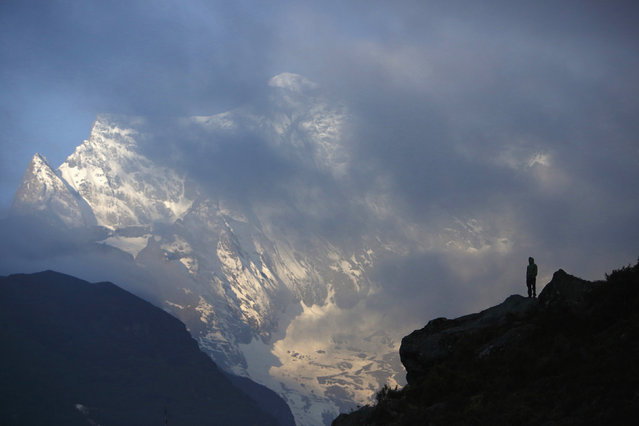 Porter Lakpa Sherpa, 42, is silhouetted as he stands in front of Mount Kongde, approximately 11155 feet above sea level in Solukhumbu District, Nepal, April 27, 2014. (Photo by Navesh Chitrakar/Reuters)