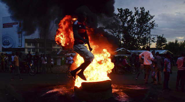 """Residents of Kisumu in Western Kenya demonstrate as they light tyres in the streets to show their displeasure with the declaration of Uhuru Kenyatta as the president following the repeat elections held on October 26.  Opposition supporters largely boycotted the voting exercise after opposition leader called it a """"Sham"""". (Photo by AP Photo/Stringer)"""