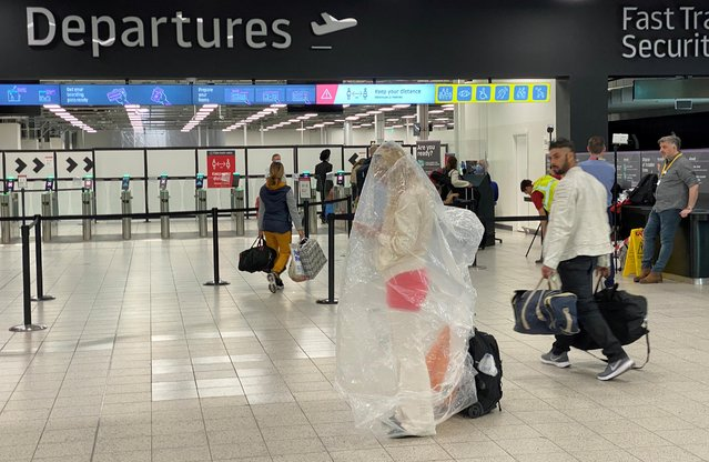 A passenger covered with a plastic bag is seen at Luton Airport, following the outbreak of the coronavirus disease (COVID-19), Luton, Britain, June 4, 2020. (Photo by Paul Childs/Reuters)