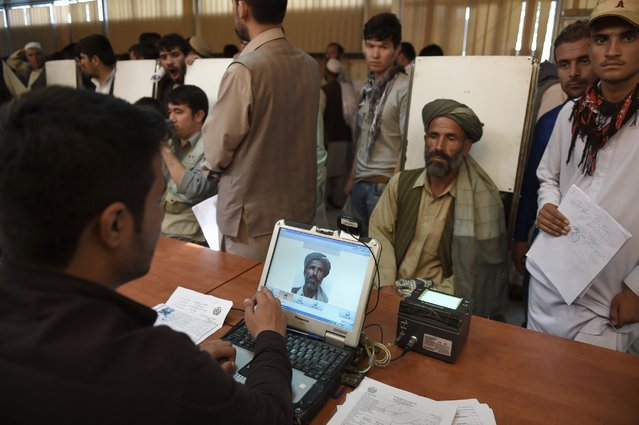 An Afghan man has his photograph taken for facial biometric information as he applies for his passport, August 25, 2015, at the passport office in Kabul. (Photo by Shah Marai/AFP Photo)