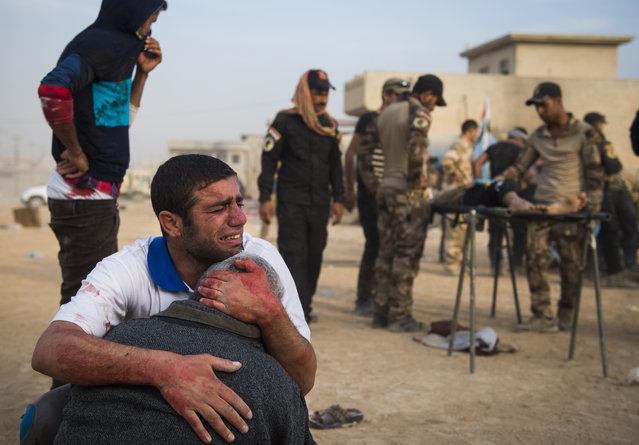 Father and grandfather of 15-year-old Shafiq mourn as Iraqi forces surround his body at an outdoor field clinic in the Samah neighbourhood in Mosul on November 13, 2016. A double barreled mortar attack killed Shafiq and seriously injured his 12-year-old neighbour Mohammed as Iraqi Special Forces 2nd division continued to battle IS forces as they pushed through the Arbagiah area and into the neigbourhood of Karkukli. (Photo by Odd Andersen/AFP Photo)