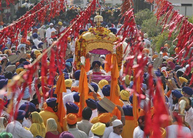 Sikh devotees carry their holy book Guru Granth Sahib in a palanquin during a religious procession inside the premises of the Golden Temple in Amritsar, India, September 14, 2015. (Photo by Munish Sharma/Reuters)
