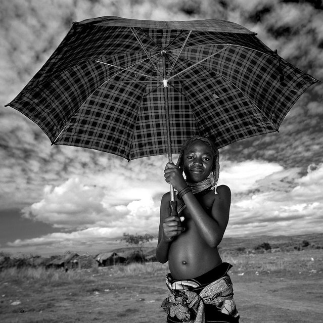 """Mumuhuila girl with umbrella – Angola. The weather was so hot! She made her traditionnal hairstyle made of cow dungs, herbs, oil, and fat, to come to the weekly market in Hale. A way to show the other people the beauty of the clan. It works!