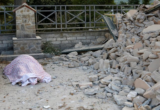 A body is covered by cloth next to rubble following a quake in Amatrice, central Italy, August 24, 2016. (Photo by Remo Casilli/Reuters)
