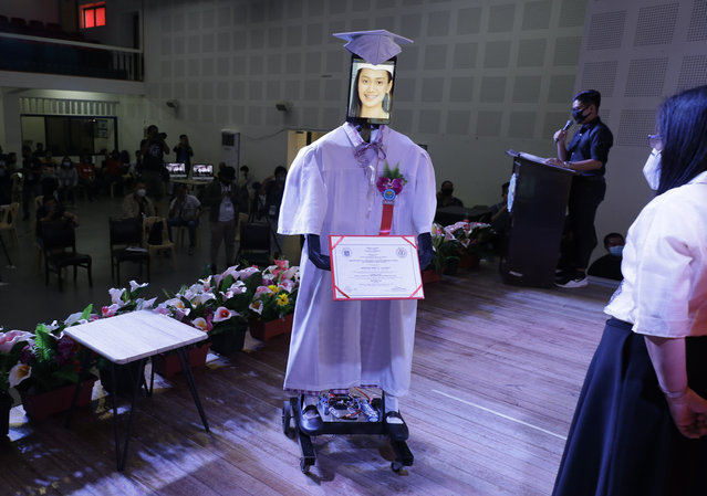 """A picture of a student is seen on a tablet that is placed on a robot during an event they called """"cyber-graduation"""" at a school at Taguig in Manila, Philippines, Friday, May 22, 2020. Robots were used to represent some 179 highschool students during an online graduation ceremony that was beamed live on Facebook to avoid mass gatherings as the school's measure to prevent the spread of the new coronavirus. (Photo by Aaron Favila/AP Photo)"""