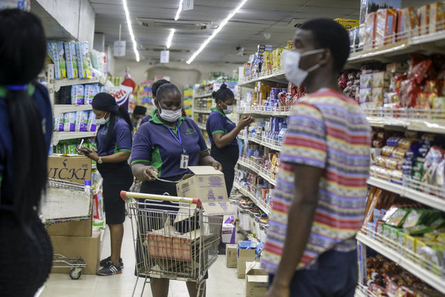 Shop assistants wearing face masks to prevent against the spread of the new coronavirus take stock in a supermarket in Lagos, Nigeria Friday, March 27, 2020. (Photo by Sunday Alamba/AP Photo)