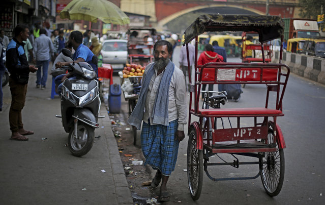"""In this November 15, 2017, photo, Mohammed Anwar, 60, a cycle rickshaw puller waits for passengers outside a railway station in New Delhi, India. Anwar, has been transporting passengers through the capital's congested streets for 35 years to support his wife and four children. Pedaling forces him to take deep breaths. """"My mouth burns while I'm working"""", he said. """"It feels like chilies in my nose"""". He said that when he washes his face each evening it is filthy. """"My eyes hurt and my nose is full of dirt"""". (Photo by Altaf Qadri/AP Photo)"""