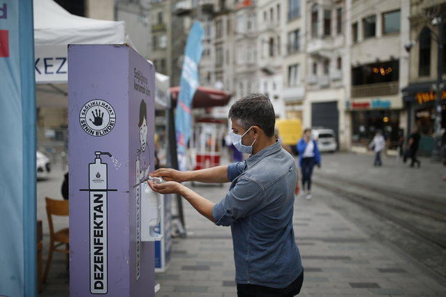 A man, wearing a protective mask against the spread of coronavirus, uses disinfectant from a public station on Istiklal street, the main shopping street in Istanbul, Thursday, June 18, 2020. (Photo by Emrah Gurel/AP Photo)