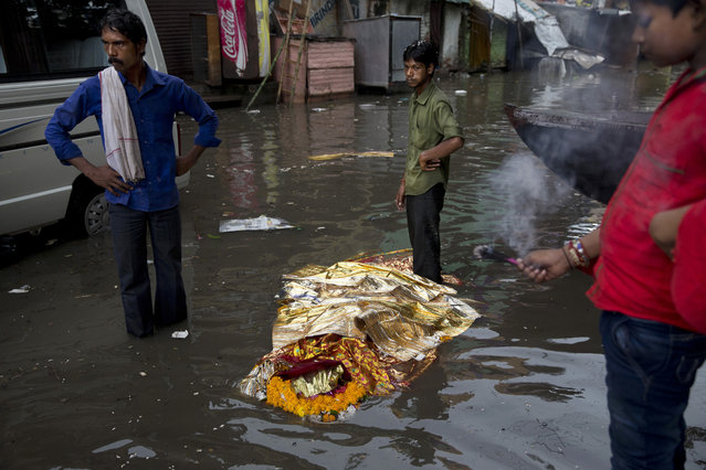 In this Friday, August 26, 2016 photo, a dead body lies in a flooded street before performing a Hindu funeral at the Harishchandra Ghat in Varanasi, India. As the mighty Ganges River overflowed its banks this past week following heavy monsoon rains, large parts of the Hindu holy town of Varanasi were submerged by floodwaters, keeping away thousands of devotees. Varanasi is a pilgrim town that Hindus visit to take a dip in the holy Ganges. Devout Hindus believe that if they are cremated on Varanasi's ghats, or steps leading to the river, they earn immediate salvation and are freed from the cycle of birth and death. The ones most affected by the floods are those who have come to the town to cremate their loved ones. (Photo by Tsering Topgyal/AP Photo)