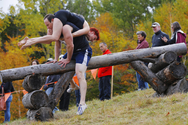 Ian Beall (L) carries Susan Beall over the second obstacle while competing in the North American Wife Carrying Championship at Sunday River ski resort in Newry, Maine October 11, 2014. REUTERS/Brian Snyder