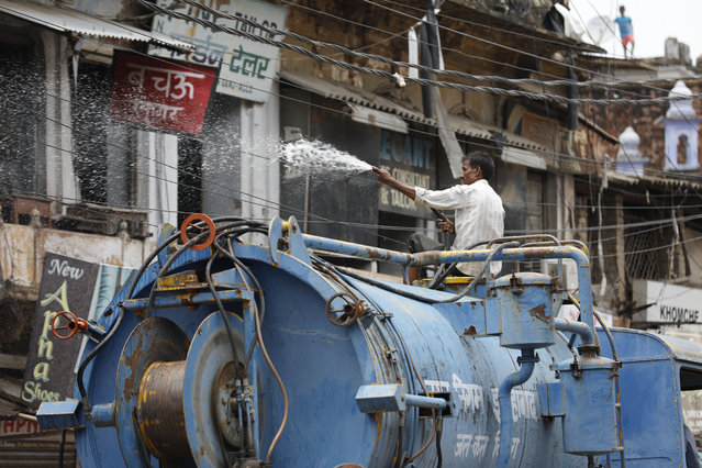A municipal worker disinfects an area amid rising COVID-19 cases in Prayagraj, India, Saturday, July 11, 2020. In just three weeks, India went from the world's sixth worst-affected country by the coronavirus to the third, according to a tally by Johns Hopkins University. India's fragile health system was bolstered during a stringent monthslong lockdown but could still be overwhelmed by an exponential rise in infections. (Photo by Rajesh Kumar Singh/AP Photo)