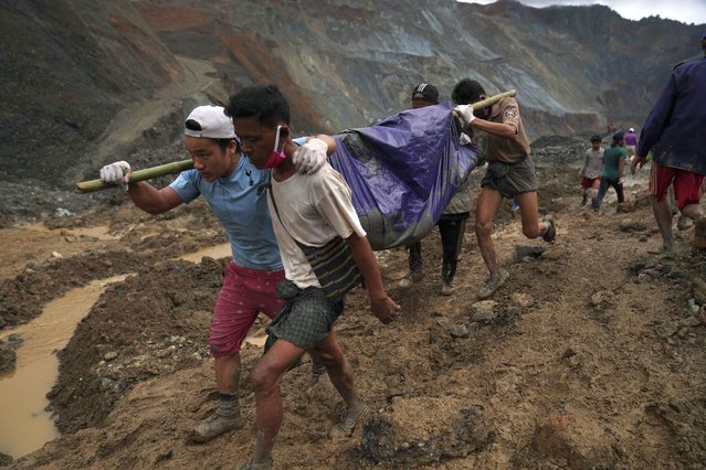 Rescue workers use poles to carry a body shrouded in blue and red plastic sheet Thursday, July 2, 2020, in Hpakant, Kachin State, Myanmar. At least 162 people were killed Thursday in a landslide at a jade mine in northern Myanmar, the worst in a series of deadly accidents at such sites in recent years that critics blame on the government's failure to take action against unsafe conditions. (Photo by Zaw Moe Htet/AP Photo)