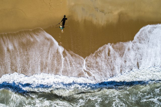 """An image made with a drone shows an ocean fisherman preparing to cast his reel in the Outer Banks, North Carolina, USA, 18 June 2020. The rough seas and hidden shoals surrounding the Outer Banks have caused more than 2,000 shipwrecks, earning it the nickname """"The Graveyard of the Atlantic"""". (Photo by Jim Lo Scalzo/EPA/EFE)"""
