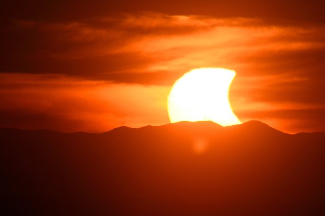 A partial solar eclipse sets behind the Blue Ridge Mountains from a vantage point on Candler's Mountain, Thursday evening, October 23, 2014, in Lynchburg, Va. (Photo by Max Oden/AP Photo/News & Daily Advance)