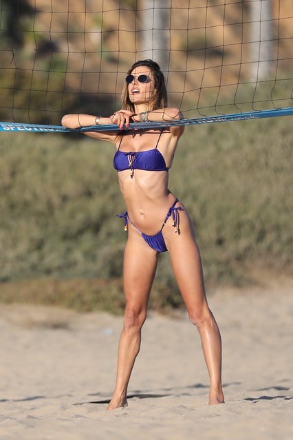 Brazilian model and television personality Alessandra Ambrosio looks gorgeous during a golden hour beach photoshoot in Malibu, CA. on July 20, 2020. The Brazilian model poses in a purple bikini with a volleyball before running around with a beach towel in the warm sunlight. (Photo by Backgrid USA)