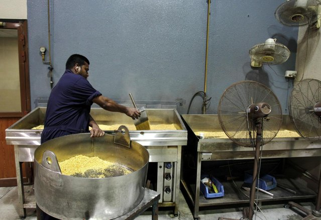 Steam rises from hot grains of gold after being melted and dropped into water as a technician pours the nuggets into a cooling container at the Emirates Gold company in Dubai, United Arab Emirates. One of the largest gold factory in the region, Emirates Gold  has processed more than two million kg of gold, worth about 108 billion U.S. dollars, into gold bars, coins and medals since it was established in 1992, Mohamad Shakarchi, managing director of the company says. (Photo by Kamran Jebreili/AP Photo)