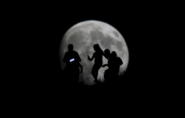 A group of hikers are seen silhouetted against the moon in Tijuana, Mexico, August 27, 2015. (Photo by Jorge Duenes/Reuters)