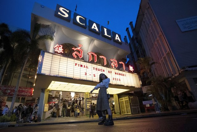A woman poses beneath the cinema marquee of the Scala theater in Friday, July 3, 2020 in Bangkok, Thailand. The Scala theater has shut its doors after 51 years as a shrine for Thai movie-goers. (Photo by Sakchai Lalit/AP Photo)