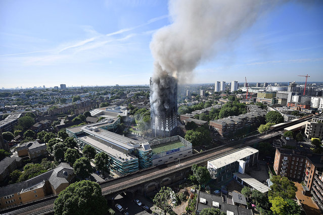 Smoke rises from the building after a huge fire engulfed the 24 storey residential Grenfell Tower block in Latimer Road, West London in the early hours of the morning in London, England on June 14, 2017. The fire claimed more than 70 lives and left hundreds homeless. (Photo by Leon Neal/Getty Images)