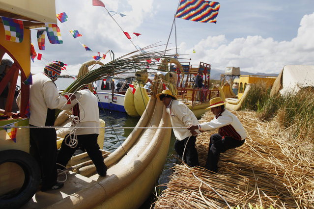 Andean people prepare a totora raft at the shores of a Uros island at Lake Titicaca before a re-enactment of the legend of Manco Capac and Mama Ocllo in Puno November 5, 2014. (Photo by Enrique Castro-Mendivil/Reuters)