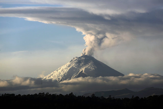 A large plume of ash and steam rises from the Cotopaxi volcano as seen from Quito, Ecuador, Thursday, October 8, 2015. The Geophysics Institute said during the first week of October the Cotopaxi has shown an increase in emission of ash and temperature, and a noted glow in the crater. (Photo by Dolores Ochoa/AP Photo)
