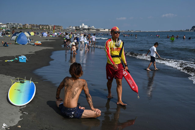 A lifeguard patrols on the beach during a summer heatwave in Fujisawa, Kanagawa prefecture on August 15, 2020. (Photo by Charly Triballeau/AFP Photo)