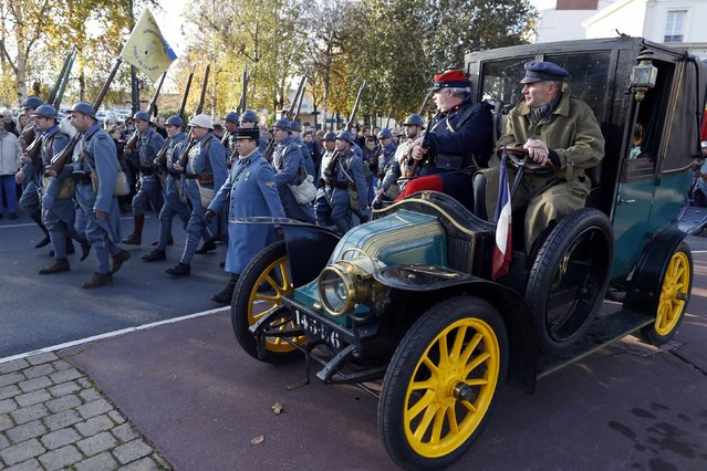 """History enthusiasts of French association """"Le Poilu de la Marne"""" pass by a vintage """"Taxi de la Marne"""" during an Armistice Day ceremony to commemorate the end of World War One at Epernay, eastern France, November 11, 2014. (Photo by Charles Platiau/Reuters)"""
