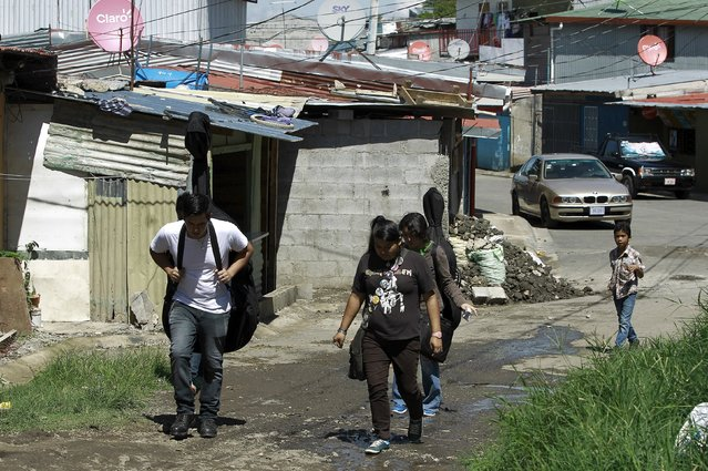 Youths walk to attend their music lessons at the Integral System of Artistic Education for Social Inclusion (SIFAIS) center in the poor neighborhood of La Carpio, Costa Rica September 12, 2015. SIFAIS center is developing a social program with the help of 156 volunteers who teach art, music, sports and education, for children and youth living in La Carpio, known for being the home to gangs, violence, drugs and social vulnerability, according to the centre. (Photo by Juan Carlos Ulate/Reuters)