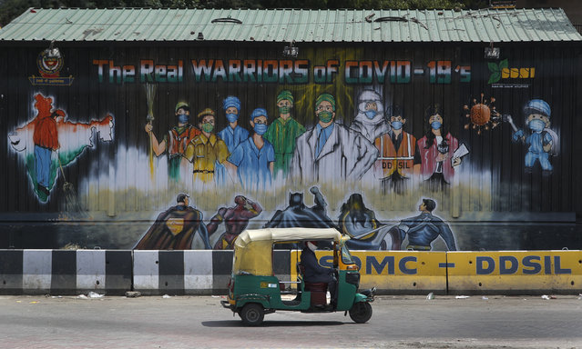 An auto rickshaw drives past a mural depicting frontline workers fighting against COVID-19 in New Delhi, India, Tuesday, September 1, 2020. India has now reported more than 75,000 infections for five straight days, one of the highest in the world, just as the government began easing restrictions to help the battered economy. (Photo by Manish Swarup/AP Photo)