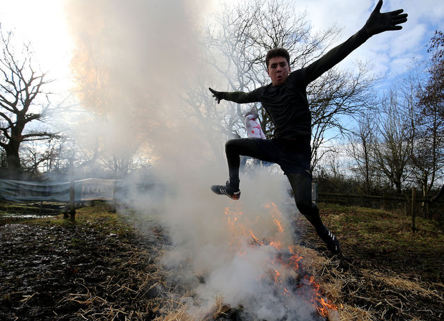 A competitor jumps through fire during the Tough Guy Mudathon event in Perton, Britain, 04 February 2018. (Photo by Nigel Roddis/EPA/EFE)