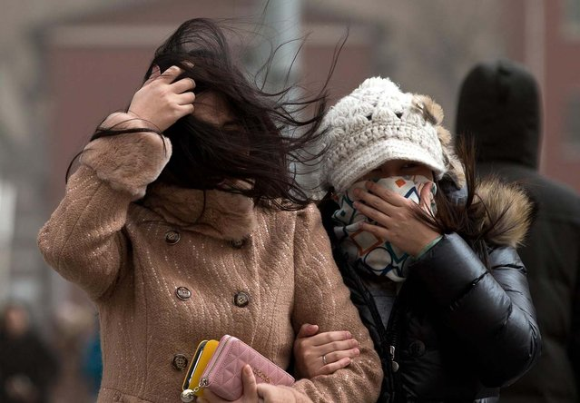 Chinese women cover their face as they brace through strong wind on a street as capital city is hit by sand storm in Beijing Thursday, February 28, 2013. (Photo by Andy Wong/AP Photo)