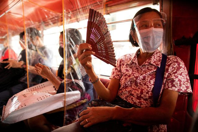 Jeepney passengers are seated in between plastic barriers, wearing face masks and face shields mandatory in public transportation, in Quezon City, Metro Manila, Philippines, August 19, 2020. (Photo by Eloisa Lopez/Reuters)