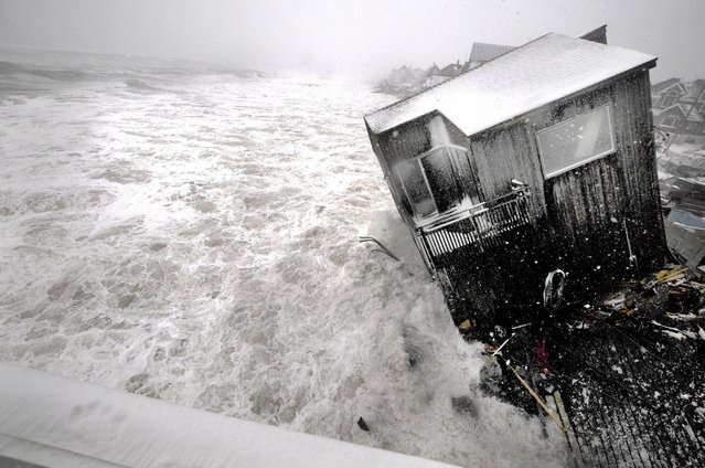A house on the Plum Island seacoast in Newbury, Mass., sits partially collapsed into the churning surf, driven by winds from a slow-moving storm centered far out in the Atlantic Ocean, at high tide Friday morning, March 8, 2013. The storm dropped up to a foot of snow in some parts of New England, caused coastal flooding in Massachusetts and slowed the morning commute in the region to a slushy crawl. (Photo by Jim Vaiknoras/AP Photo/Newburyport Daily News)