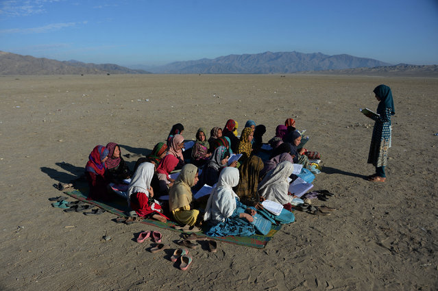 In this photograph taken on December 23, 2017 Afghan school children take part in a lesson at an open-air school at the Gambiri Refugee Camp in Laghman province. Millions of dollars have been spent on the education sector in Afghanistan, but there are countless schools across the country that are in the same predicament – either in tents or in the open air. (Photo by Noorullah Shirzada/AFP Photo)