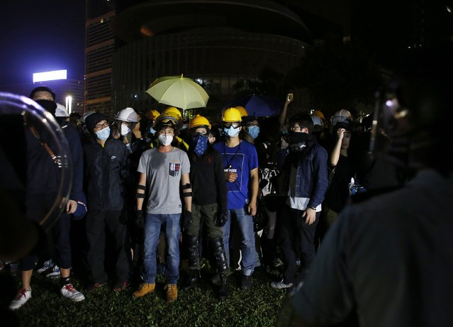 Pro-democracy protesters stand in front of riot police during a confrontation outside government headquarters in Hong Kong early December 1, 2014. (Photo by Bobby Yip/Reuters)