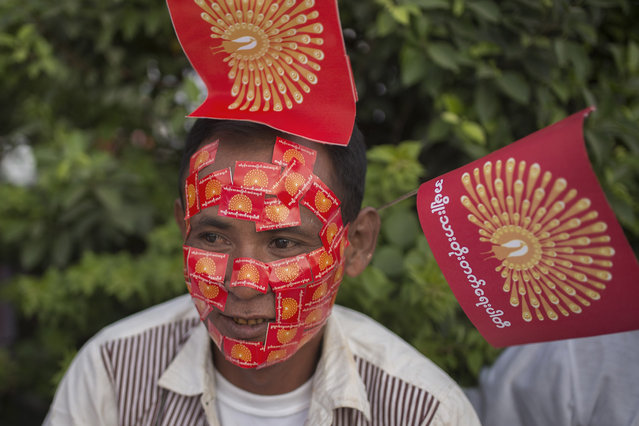 A supporter of National Development Party (NDP) displays stickers of party flags stuck to their face during an election campaign in Mandalay, Myanmar, Sunday, October 25, 2015. Myanmar's general elections are scheduled for November 8, 2015, the first since a nominally civilian government was installed in 2011. (Photo by Hkun Lat/AP Photo)