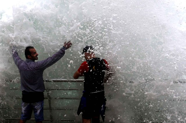 Lebanese men stand in front of waves crashing over them on the seafront at the Corniche, or waterfront promenade, in Beirut, Lebanon, Sunday, October 25, 2015. (Photo by Hassan Ammar/AP Photo)