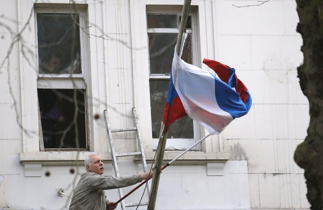 A man works to untangle the national flag flown from the Russian Embassy, after it became entangled on its staff at the embassy in London, Wednesday, March 14, 2018. Britain announced Wednesday it will expel 23 Russian diplomats, the biggest such expulsion since the Cold War, and break off high-level contacts with the Kremlin over the nerve-agent attack on a former spy and his daughter in an English town. (Photo by Alastair Grant/AP Photo)