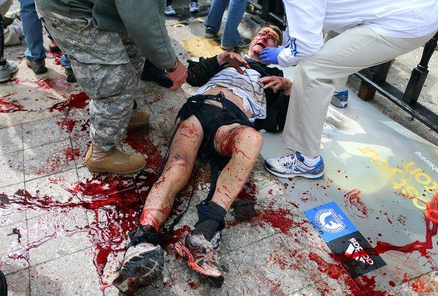 The scene moments after the first explosion near the finish line of the Boston Marathon. (Photo by John Tlumacki/The Boston Globe)